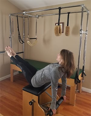 woman performing exercises on the pilates chair
